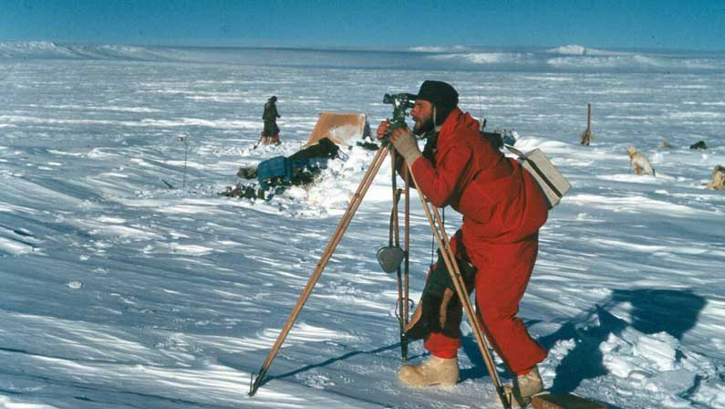 Photo by Richard Ruker. Syd Kirkby using a theodolite in Enderby Land 1960